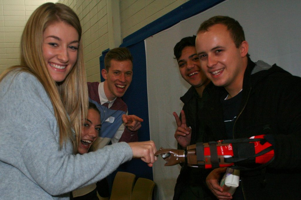 Catholic visitor Belinda Maric, Sarah Kelley, Russell Willoughby, Thomas Ausega and Perry Christeson celebrate making their prosthetic hand.